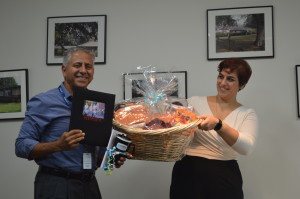 John Suarez Sr. Manager receives the First Place basket from Community & Development Coordinator, Francesca Cwynar